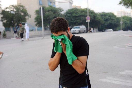 Un homme protège son visage des gaz lacrymogènes lors d'une manifestation à Tunis contre la chaîne Nessma TV, le 14 octobre 2011 AFP Fethi Belaid