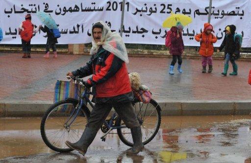 Un Marocain marche devant un panneau pour les prochaines élections législatives, le 22 novembre 2011 à Oulmès. AFP Abdelhak Senna