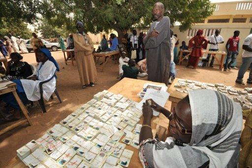 Une femme attend les votants, des cartes électorales non réclamées devant elle le 23 février 2012 à Touba AFP Issouf Sanogo