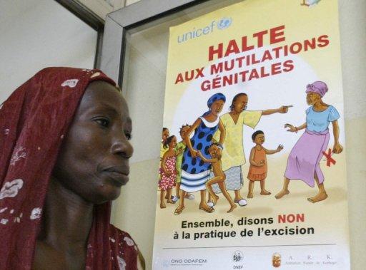Une femme devant une affiche de l'Unicef prônant l'arrêt de l'excision, le 17 novembre 2005 à Abidjan (Côte d'Ivoire) AFP/Archives Kambou Sia