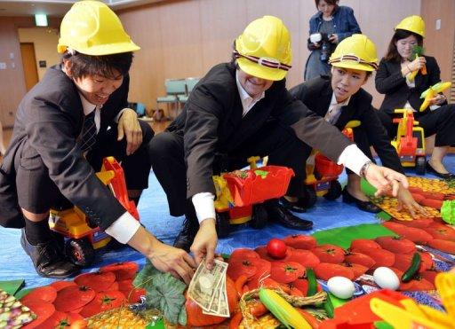 Des militants de l'ONG Oxfam jouent une saynète pour dénoncer l'accaparement des terres dans le tiers-monde, le 10 octobre 2012 à Tokyo AFP Yoshikazu Tsuno