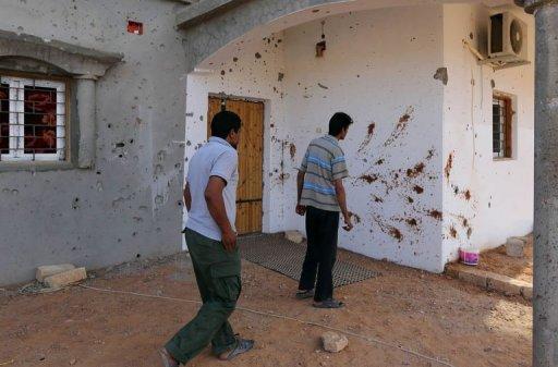 Des Libyens devant un mur taché de sang à Bani Walid, le 11 octobre 2012 AFP Mahmud Turkia
