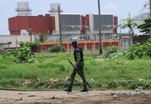 Un soldat ivoirien passe devant la centrale thermique d'Azito, dans le quartier de Yopougon à Abidjan, le 15 octobre 2012 AFP Sia Kambou