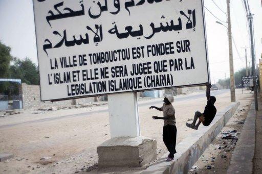 Des enfants jouent devant un panneau portant un message de la Charia, le 31 janvier 2013 à Tombouctou, au Mali AFP Fred Dufour