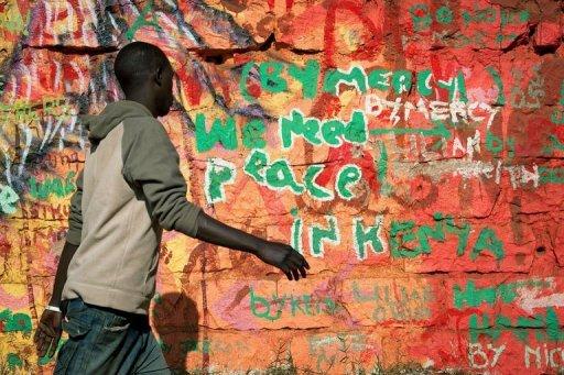 Un Kényan passe devant un graffiti