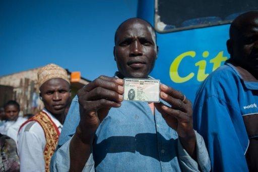 Un Kényan montre sa carte d'identité dans la file d'attente devant un bureau de vote à Nairobi, le 4 mars 2013 AFP Will Boase