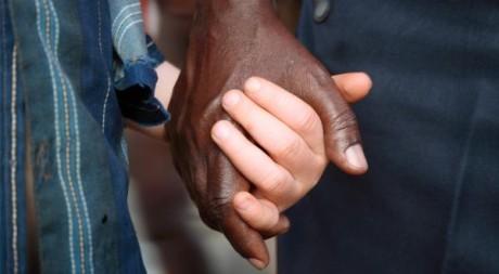 Un bénévole tient la main d'un enfant albinos dans une école pour handicapés, en Tanzanie. Ho New/Reuters
