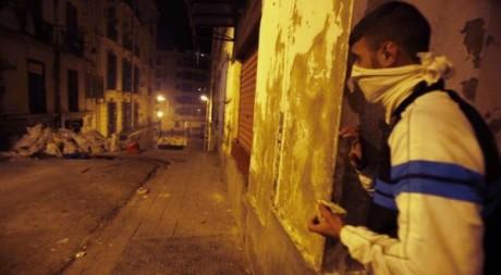 Un jeune Algérien tient une pierre durant les affrontements avec la police à Alger, dans le quartier de Bab el-Oued, le 6 janvie