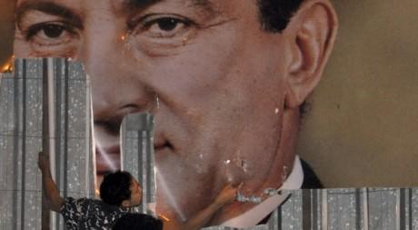 Un manifestant antigouvernement décolle une affiche d'Hosni Mubarak à Alexandrie, le 25 janvier 2011.
