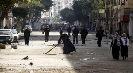 Un homme balaie tandis que des manifestants se dirigent vers le square Tahrir le 6 février 2011 au Caire. REUTERS/Dylan Martinez