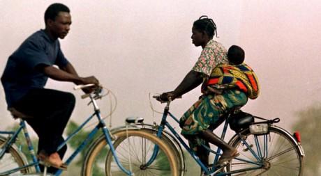 Une femme part au travail à vélo avec son bébé, à Ouagadougou, Burkina Faso. REUTERS/Juda Ngwenya
