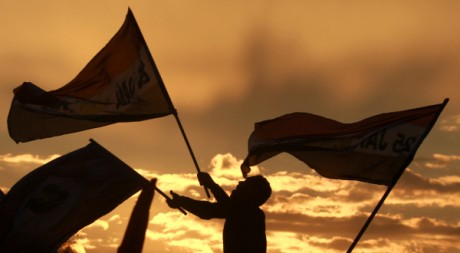 Un manifestant agite un drapeau après le discours d'un général égyptien place Tahrir le 10 février 2011. REUTERS/Yannis Behrakis