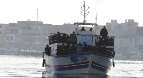Des immigrés clandestins tunisiens arrivent sur l'île italienne de Lampedusa, le 13 février 2011. REUTERS/Antonio Parrinello