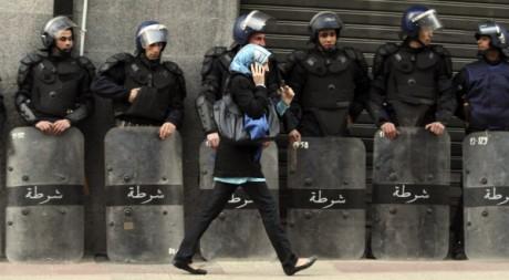 Une femme passe devant des policiers anti-émeutes lors d'une manifestation à Alger, le 12 février 2011. REUTERS/Louafi Larbi