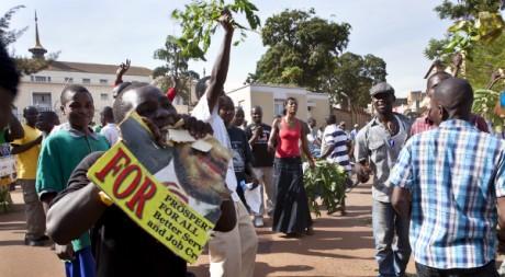 Un opposant mange un poster à l'effigie d'un candidat pro-Museveni, en Ouganda. © Ines Della Valle, tous droits réservés.