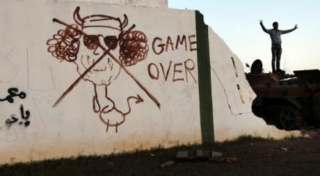 Une caricature de Kadhafi sur un mur à Benghazi, Libye, le 11 mars 2011. REUTERS/Finbarr O'Reilly