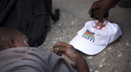 Un homme ramasse la casquette d'Ivarol Louis, le jeune homme à terre, à Port-au-Prince, le 25 nov 2010. REUTERS/Allison Shelley