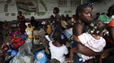 Des Ivoiriens attendent le bus à Abidjan pour fuir vers la campagne, le 20 mars 2011. REUTERS/Luc Gnago