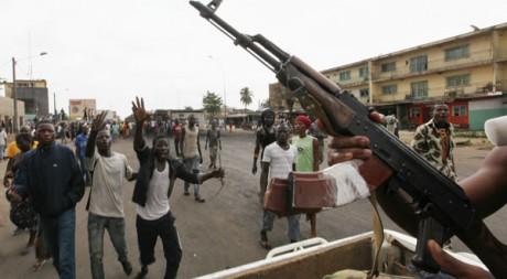 Des combattants pro-Ouattara arrivant dans une rue d'Abobo, un quartier d'Abidjan, le 27 mars. Reuters/Luc Gnago