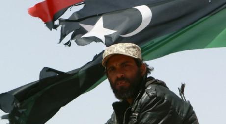 Un soldat de la rébellion libyenne devant un drapeau du royaume de Libye. Amr Dalsh / Reuters