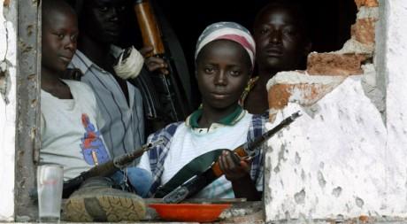 Des enfants armés pour combattre à Bunia, à l'est de la RDC, juin 2003. REUTERS/Jacky Naegelen