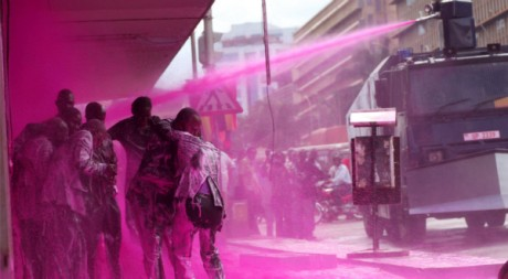 La police a aspergé d'eau colorée rose les leaders de l'opposition, le 10 mai à Kampala. REUTERS/James Akena