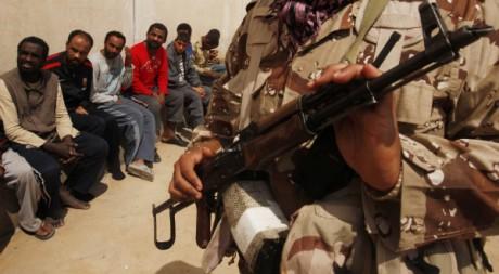 Un rebelle libyen garde des prisionniers suspectés d'être des mercenaires pro-Kadhafi, en mars à Benghazi. REUTERS/Suhaib Salem