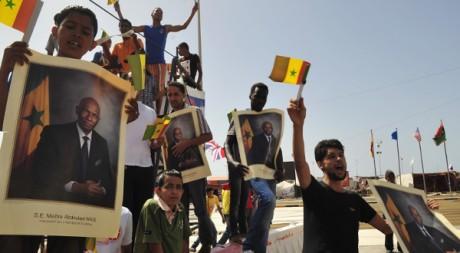Des habitants de Benghazi brandissent des posters d'Abdoulaye Wade lors de sa visite, le 9 juin 2011. REUTERS/STR New