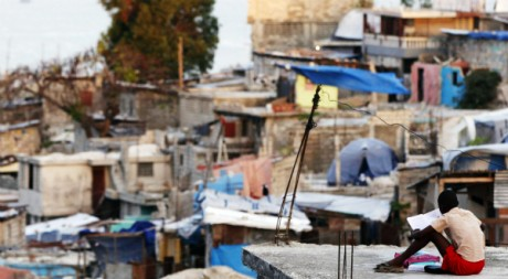Un jeune garçon lit un livre sur le toit de sa maison à Port-au-Prince, Haïti, le 17 mars 2011. REUTERS/Shannon Stapleton
