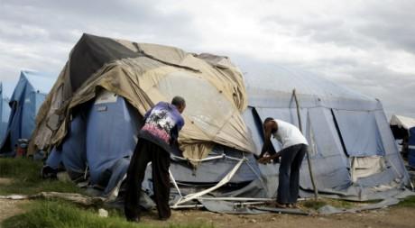 Des hommes tentent de rapiécer leurs tentes à Cité Soleil, Haïti, le 4 août 2011. REUTERS/Swoan Parker