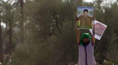 Un homme brandit le portrait de Mouammar Kadhafi, à Majar, en Libye, le 10 août 2011. REUTERS/Caren Firouz