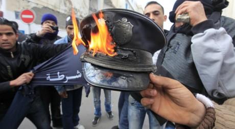 Des manifestants brûlent une casquette de policier, Tunis, le 14 janvier 2011. REUTERS/Zohra Bensemra