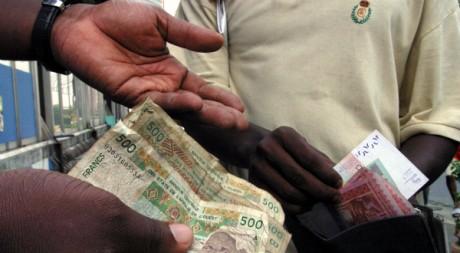 Des Africains échangent des francs CFA, en décembre 2004. REUTERS/Thierry Gouegnon