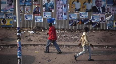 Des Congolais marchent devant des panneaux électoraux à Kinshasa, le 25 novembre 2011. REUTERS/Finbarr O'Reilly