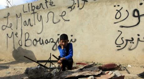 Un garçon devant un mur plein de graffitis à Sidi Bouzid, ville de Mohamed Bouazizi, 19 janvier 2011. REUTERS/Zohra Bensemra