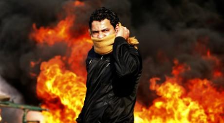 Un manifestant au Caire, devant une barricade en flammes, le 28 janvier 2011. REUTERS/Goran Tomasevic.