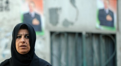 Une femme marche devant des posters de campagne d&#039;Abdelaziz Bouteflika le 24 mars 2009.  AFP PHOTO/FAYEZ NURELDINE