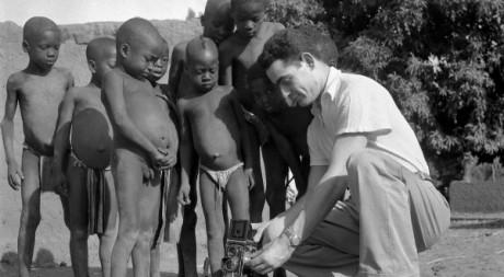 Un photographe montre le fonctionnement de son appareil photographique à quelques petits africains à Bamako, en 1951. AFP