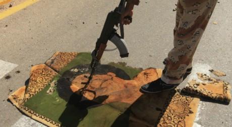 Un combattant pointe son arme sur une tapisserie à l'effigie de Kadhafi à Syrte le 12 octobre 2011. Reuters/Esam Al-Fetori