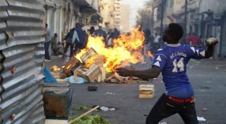 A Dakar, un manifestant lance une pierre en direction de la police, le 18 février. REUTERS/Stringer.