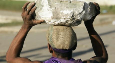 Un ouvrier ramasse des gros blocs de pierre sur l'île de Cuba, 17 décembre 2009. Reuters/Desmond Boylan