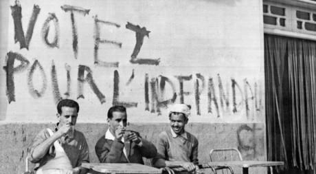 Des Algériens prennent leur café sous une inscription appelant à voter pour l'indépendance à Alger le 17 juin 1962. AFP/FARENC