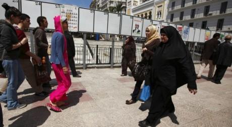 Des femmes marchent devant pancartes électorales à Alger le 19 avril 2012. Reuters/ Zohra Bensemra