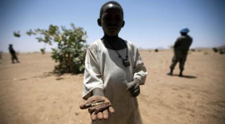 Un enfant tenant des douilles ramassées, Rounyn, Nord Darfour, 27 mars 2011 REUTERS/Handout