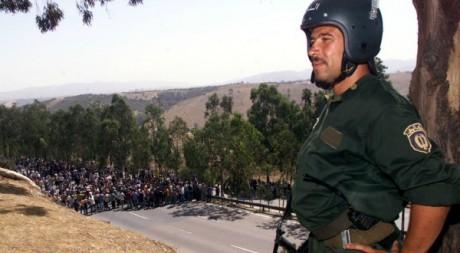 Un policier regarde la manifestation pacifique de jeunes berbères sur une route à l'est d'Alger, le 8 août 2001. REUTERS/StrOld