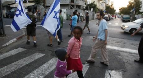 Des enfants africains traversent une manifestation contre les immigrés africains à Tel Aviv le 30 mai 2012.  Reuters/Baz Ratner