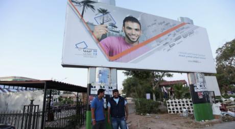 De jeunes Libyens devant une affiche électorale à Benghazi, juin 2012. © Esam Al-Fetori/Reuters