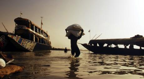 Travailleur portant un sac de céréales à destination d'une pirogue sur le fleuve Niger à Mopti, février 2007, REUTERS/F.Lorganda