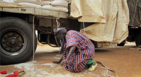 Un homme récupère des grains de riz tombés d'un convoi à Gao, nord du Mali, 18/06/2012 REUTERS/Stringer