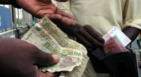 Deux hommes échangent de l'argent à Abidjan, 31/12/2004, REUTERS/Thierry Gouegnon